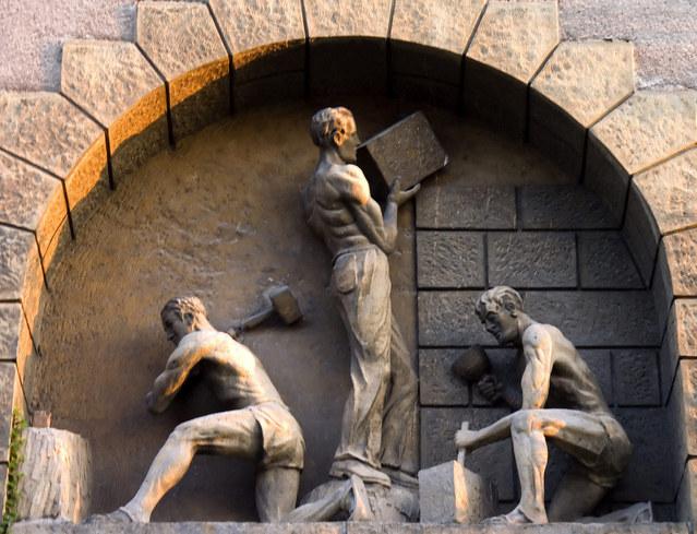 kamenné sochy dělníků stavějící zeď