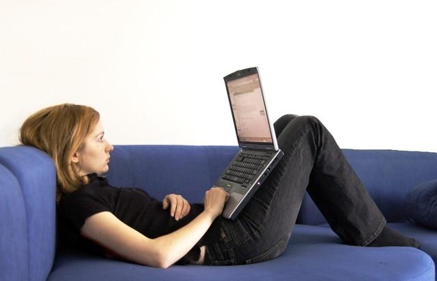 žena sedící na pohovce a pracující na notebooku